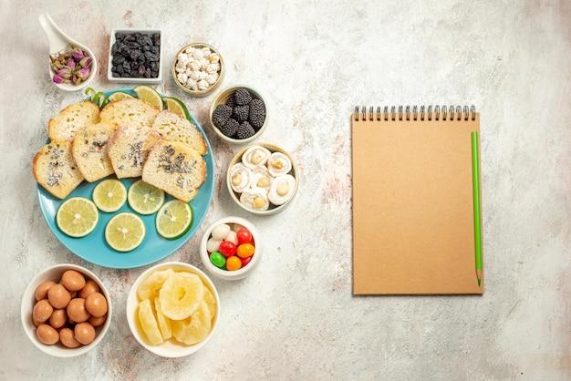 Vista dall'alto da lontano torta al limone sette ciotole di caramelle accanto al quaderno di crema con piatto a matita verde di pezzi di torta al limone sul tavolo