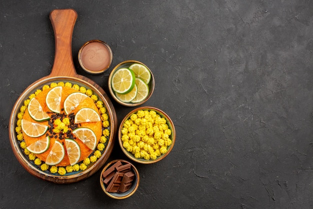 검은 탁자에 감귤류 과일과 다양한 라임 조각이 든 그릇을 곁들인 식욕을 돋우는 케이크와 멀리 있는 라임과 사탕의 꼭대기 전망