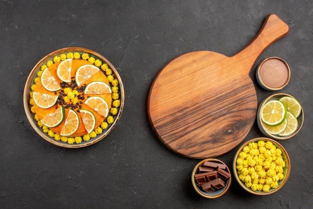 멀리 있는 라임과 사탕 그릇의 다양한 과자 초콜릿 조각과 나무 주방 보드 옆에 있는 초콜릿 크림, 식욕을 돋우는 감귤류 과일이 있는 케이크