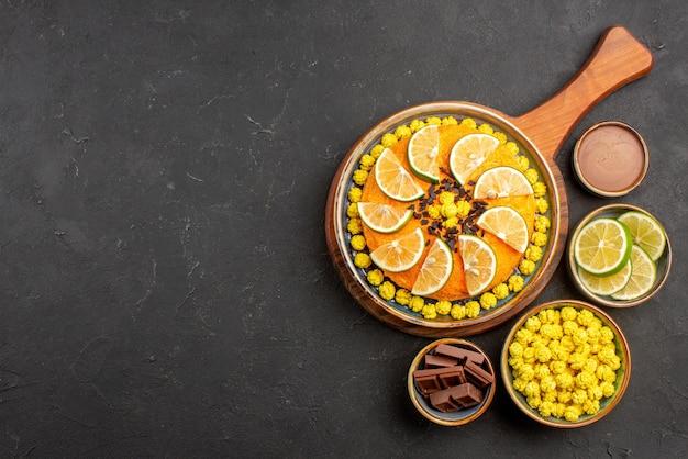 검은 탁자에 있는 도마에 감귤류 과일이 있는 케이크 옆에 있는 다양한 라임 조각과 사탕 그릇의 꼭대기 전망