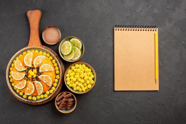 Vista dall'alto da lontano lime e caramelle appetitosa torta con agrumi accanto alla matita gialla e quaderno crema e ciotole di diversi dolci fette di lime sul tavolo nero