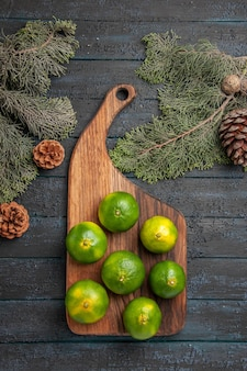 ボード上の遠くのライムからの上面図木の枝とコーンの隣のキッチンボード上の緑のライム