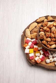 Top view from afar nuts on the board sweet peanuts in bowl and different sweets on the kitchen board on the table