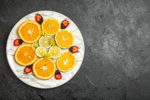 遠くからの上面図オレンジとレモンチョコレートで覆われたイチゴは、暗いテーブルの白いプレートにレモンオレンジをスライスしました