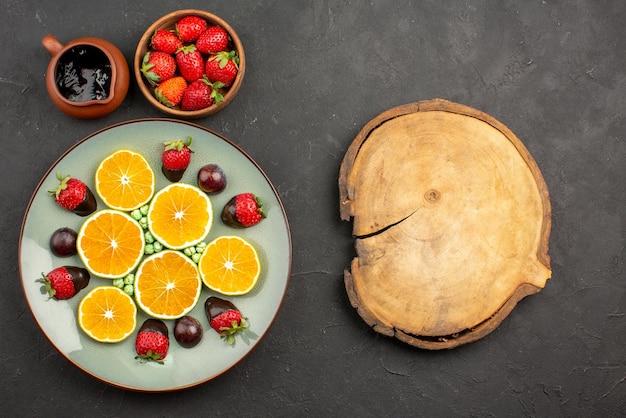 Vista dall'alto da lontano salsa di cioccolato e arancia e fragole accanto a caramelle verdi arancioni tritate alla fragola ricoperte di cioccolato e tagliere di legno