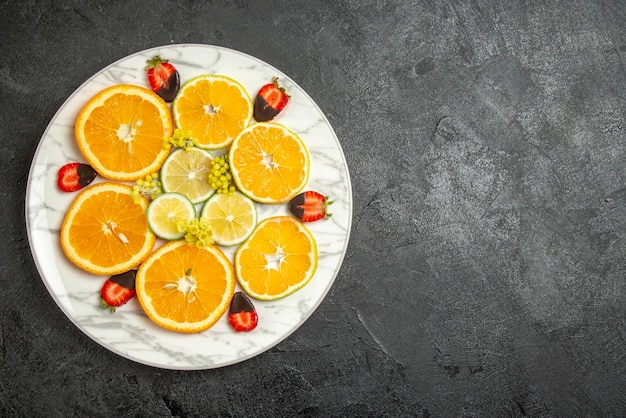 Top view from afar orange and lemon chocolate-covered strawberries sliced lemon orange on white plate on the dark table