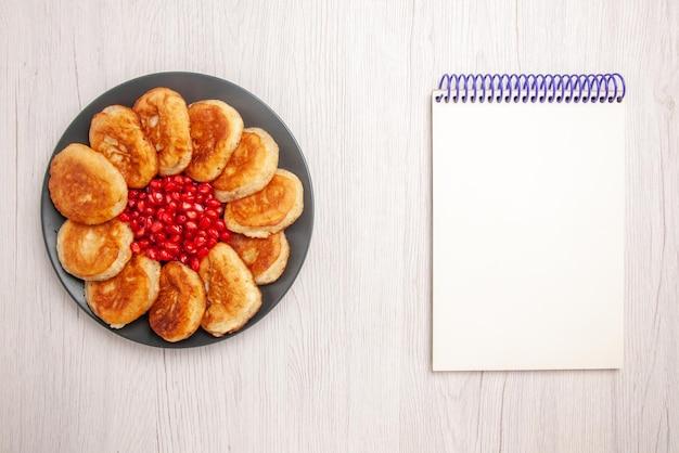 흰색 탁자에 있는 흰색 공책 옆에 있는 검은 접시에 석류를 넣은 식욕을 돋우는 팬케이크의 꼭대기 전망