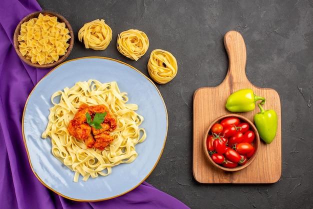 紫色のテーブルクロスのパスタのボウルとパスタのプレートの横にある木製のまな板の遠方のパスタとミートボールペッパーとトマトからの上面図
