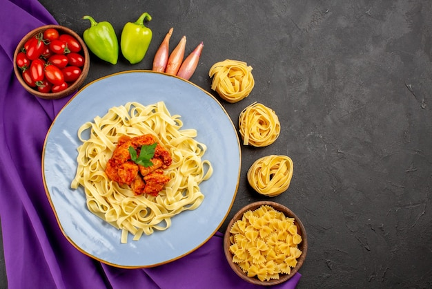 紫色のテーブルクロスのパスタとパスタのプレートの横にあるトマトボールペッパーオニオンの遠くのパスタとミートボウルからの上面図
