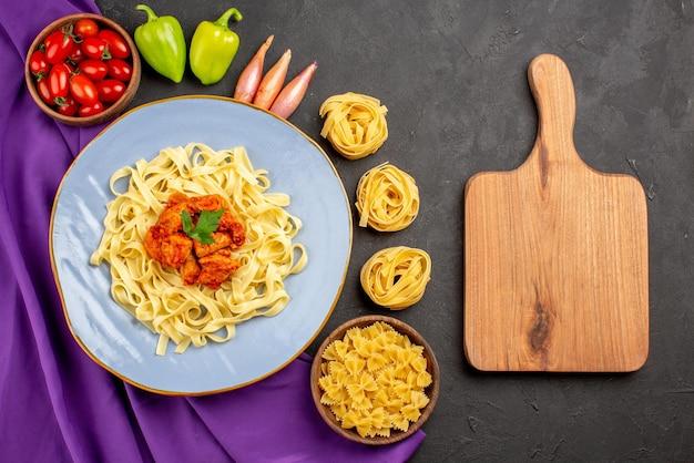 木製のまな板パスタと紫色のテーブルクロスのパスタのプレートの横にある遠くのパスタとトマトボールペッパーオニオンのミートボウルからの上面図