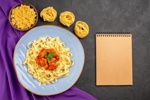 暗い背景のクリーム色のノートの横にある紫色のテーブルクロスのパスタとパスタのミートボウルとパスタグレイビーと肉のプレートからの上面図