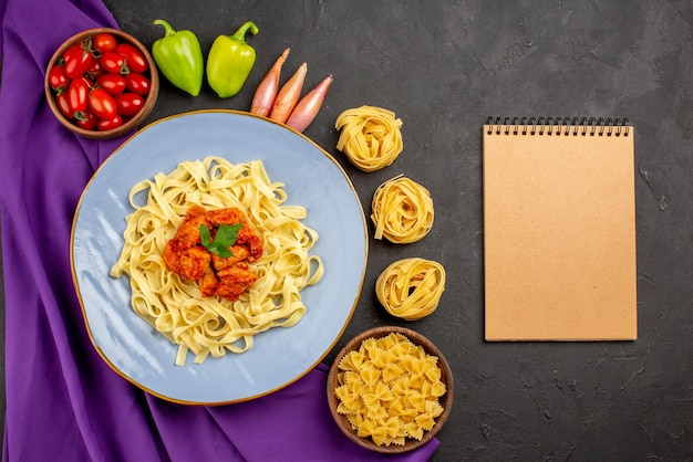 Top view from afar pasta and meat bowl of tomatoes ball pepper onion next to the cream notebook pasta and plate of pasta on the purple tablecloth