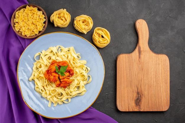 Vista dall'alto da lontano ciotole di pasta e carne di pasta e piatto di sugo di pasta e carne sulla tovaglia viola accanto al tagliere