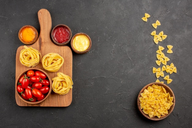 Вид сверху издалека макароны на доске помидоры и макароны на разделочной доске рядом с разными видами соусов и миской макарон на столе