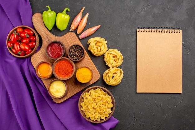 Vista dall'alto da lontano pasta e pomodori spezie e salse in ciotole sul tagliere cipolla ciotola di pomodori pallina pepe e pasta accanto al quaderno di crema sul tavolo