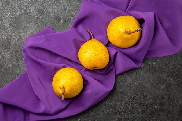 テーブルクロスの遠い梨からの上面図テーブル中央の紫色のテーブルクロスの3つの梨を食欲をそそる 無料写真
