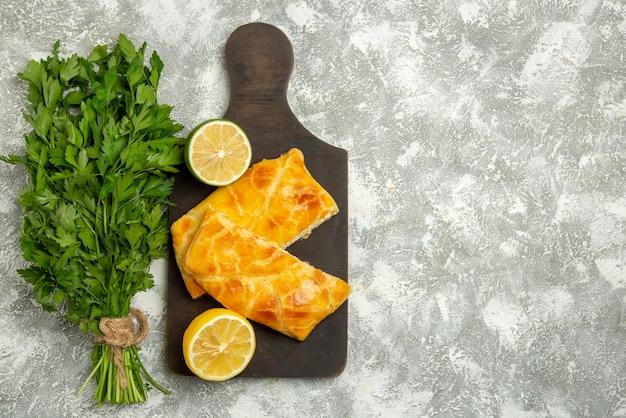 テーブルの左側にあるハーブの横にある木製のまな板にある遠くのパイハーブチーズライムパイとレモンからの上面図