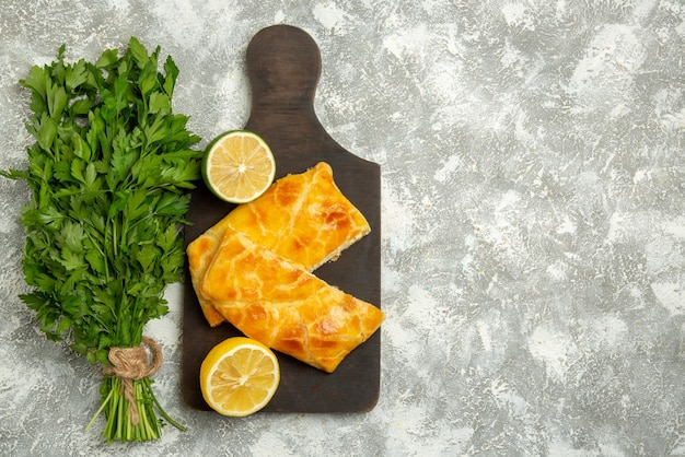 Vista dall'alto da lontano torte alle erbe formaggio torte al lime e limone sul tagliere di legno accanto alle erbe sul lato sinistro del tavolo