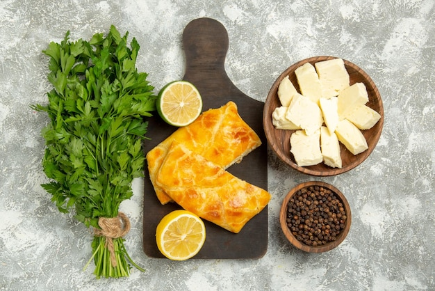 Top view from afar pies herbs cheese pies and lemon on the wooden board next to the bowls of black pepper cheese and herbs on the grey table