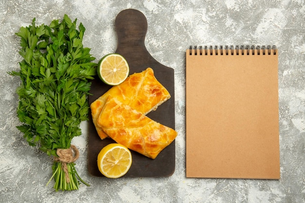 Top view from afar pies herbs cheese pies and lemon on the wooden board next to the cream notebook on the table
