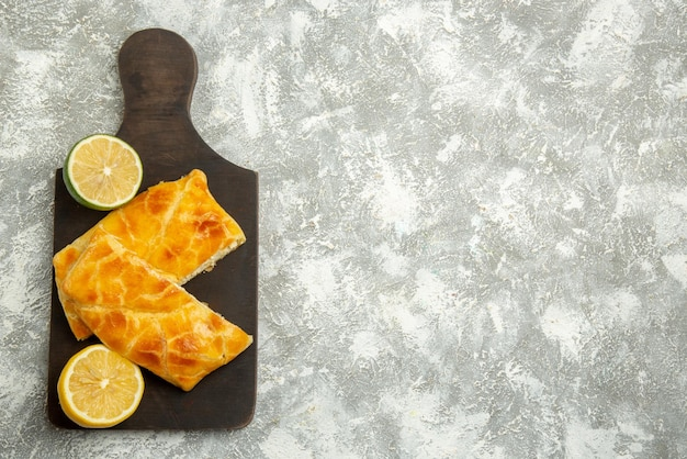 テーブルの左側にある暗い木製のまな板の食欲をそそるパイレモンとライムに乗って遠くのパイからの上面図