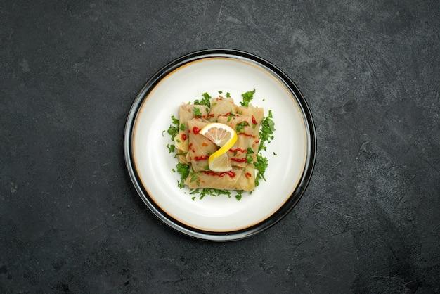검은 탁자 중앙에 있는 흰색 접시에 레몬 허브와 소스를 곁들인 식욕을 돋우는 배추를 채운 멀리 접시의 꼭대기