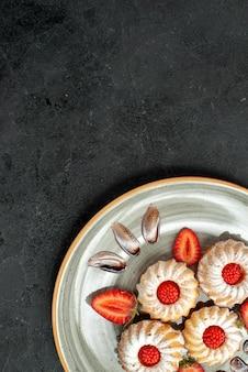 Вид сверху издалека тарелка печенья белая тарелка аппетитного печенья с шоколадом и клубникой на темной поверхности