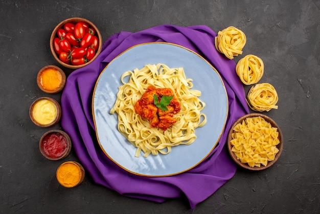 소스 토마토와 다양한 종류의 소스 그릇 옆에 보라색 식탁보에 파스타 고기와 그레이비가 있는 파스타 파란색 그릇의 멀리 접시에서 상위 뷰