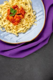 식탁보에 파스타 고기와 그레이비가 있는 파스타 파란색 그릇의 멀리 접시에서 상위 뷰