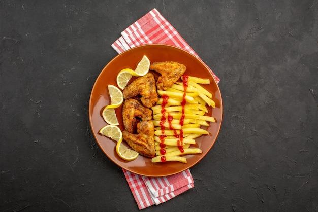 Вид сверху на тарелку на скатерти оранжевая тарелка с куриными крылышками, кетчупом, картофелем фри и кусочками лимона на розово-белой клетчатой скатерти в центре темного стола