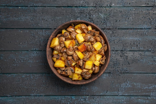 Vista dall'alto da lontano piatto con cibo marrone piatto con funghi e patate sul tavolo grigio
