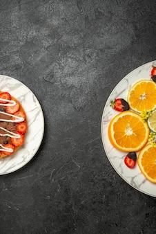 柑橘系の果物とチョコレートで覆われたイチゴのプレートの横にチョコレートとイチゴとテーブルケーキの遠方のプレートからの上面図
