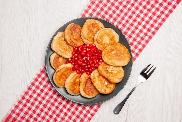 Top view from afar pomegranate appetizing pancakes and seeds of pomegranate on the checkered tablecloth and a fork on the table
