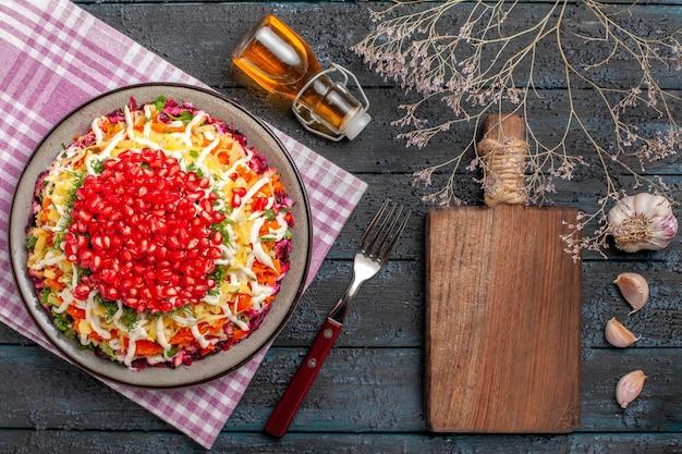 Вид сверху на гранат в тарелке, блюдо на клетчатой скатерти рядом с разделочной доской, вилка, ветки деревьев, чеснок, бутылка масла на столе