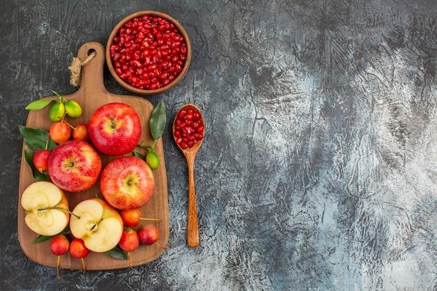 Вид сверху издалека гранат семена граната ложка доска яблоки вишня
