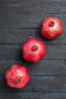 나무 회색 탁자 중앙에 있는 멀리 붉은 석류 익은 석류의 꼭대기