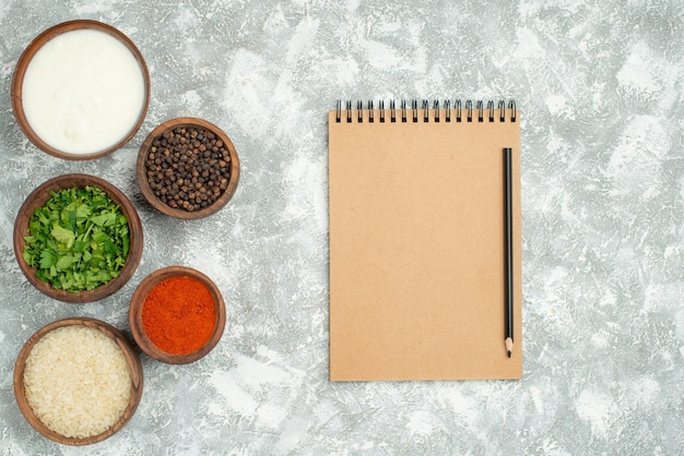 테이블 왼쪽에 있는 크림 노트와 연필 옆에 있는 쌀 허브 사워 크림 향신료와 검은 후추의 멀리 있는 쌀과 향신료 그릇