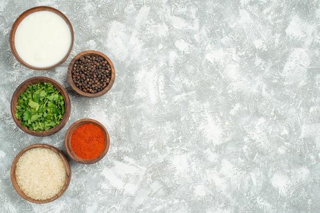 테이블 왼쪽에 있는 쌀 허브 사워 크림 향신료와 검은 후추의 멀리 쌀과 향신료 그릇에서 상위 뷰