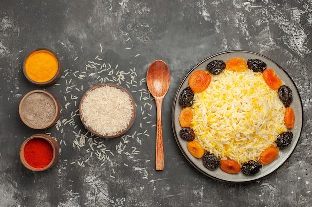 쌀의 말린 과일 숟가락 그릇 멀리 쌀 다채로운 향신료 쌀에서 상위 뷰