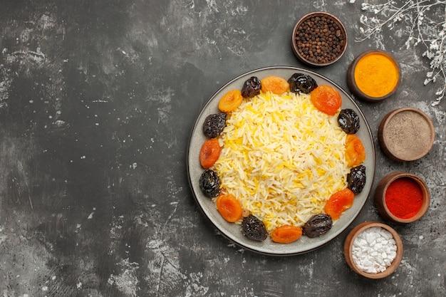 다채로운 향신료 나뭇 가지의 접시 그릇에 멀리 쌀 쌀과 말린 과일에서 상위 뷰