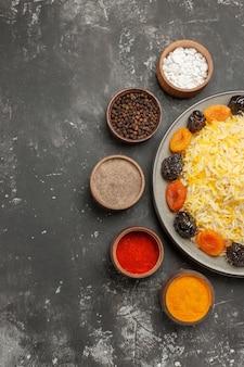 향신료 그릇 옆에 접시에 쌀 쌀과 말린 과일 멀리에서 상위 뷰
