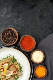 흰색 및 노란색 소스 그릇 옆에 레몬 허브와 소스를 곁들인 박제 양배추의 식탁보 접시에 있는 멀리 소스에서 보는 상단 보기 어두운 탁자에 있는 회색 식탁보에 검은 후추 다채로운 향신료