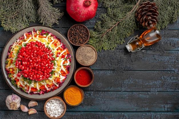 Vista dall'alto da lontano spezie spezie colorate pepe nero bottiglia di olio aglio rami di abete con coni e piatto di cibo con melograno