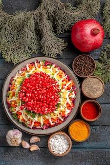 멀리서 향료 다채로운 향신료 검은 후추 마늘 가문비나무 가지와 석류가 든 음식 접시에서 상위 뷰