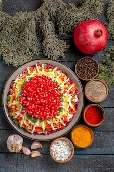 Top view from afar spices colorful spices black pepper garlic spruce branches and plate of food with pomegranate