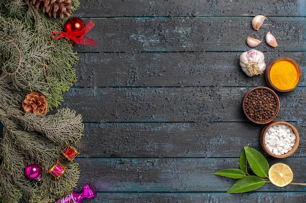 Вид сверху издалека специи на столе еловые ветки с шишками и елочные игрушки чаши со специями, чесночным маслом, лимоном на сером столе