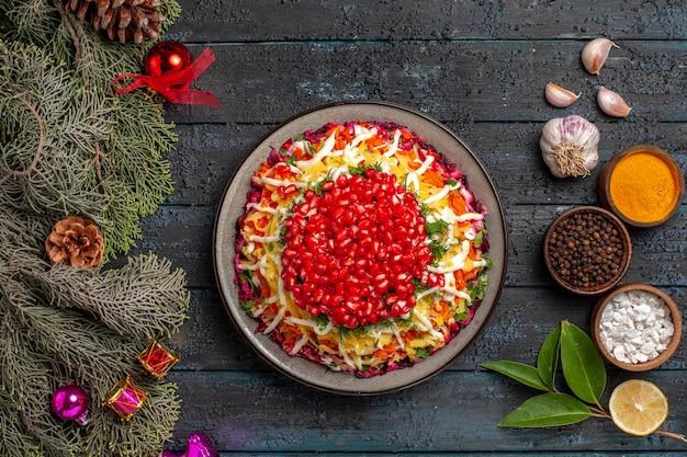 Vista dall'alto da lontano spezie sul tavolo gustoso piatto con rami di abete rosso di melograno con coni e giocattoli dell'albero di natale ciotole di spezie aglio olio limone sul tavolo