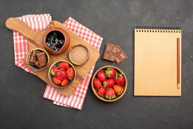 멀리 보이는 딸기와 초콜릿 딸기 초콜릿 크림은 딸기 접시 옆에 있는 식탁보와 연필로 된 공책 옆에 있는 커팅 보드에 있는 그릇에 있습니다.