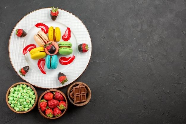 遠くからの平面図イチゴとマカロンの食欲をそそるイチゴのプレート暗いテーブルの上のお菓子のボウルの横にあるフレンチマカロンソース