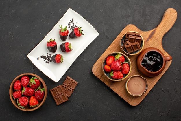 Vista dall'alto da lontano fragole ciotola di fragole barrette di cioccolato piatto di fragole ricoperte di cioccolato accanto alle ciotole di crema al cioccolato e fragole sul tagliere